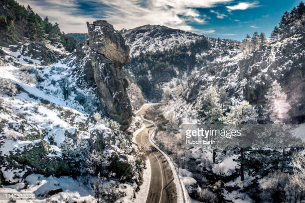 road and mountain landscape in winter with a frost forest and a man standing on the road looking to the views - provinz leon stock-fotos und bilder