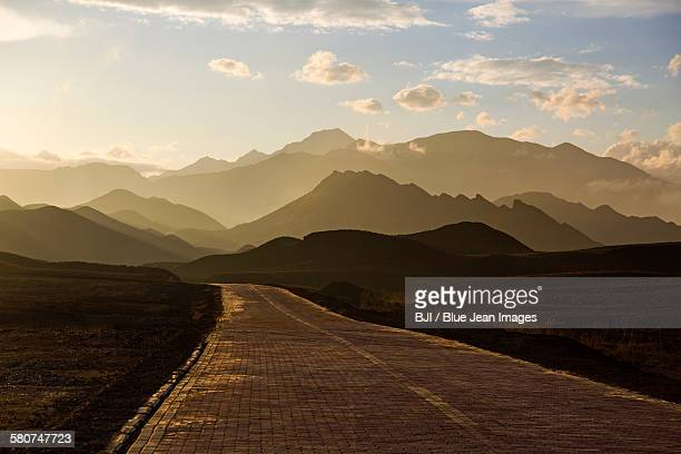 road and mountain range in gansu province, china - gansu province stock pictures, royalty-free photos & images