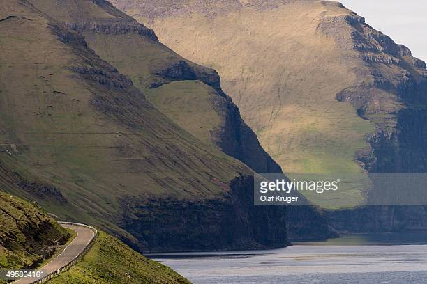 Road and mountains towering from the sea, Kalsoy, Norooyar, Faroe Islands, Denmark
