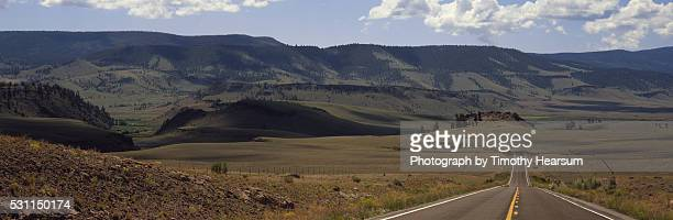 road and mountains with sky and clouds - timothy hearsum stock pictures, royalty-free photos & images