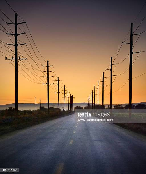 Road and power lines at sunset
