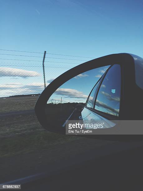 Road And Sky Reflecting In Side-View Mirror Of Car