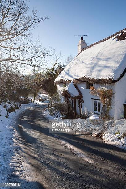 Road and Snow Covered Thatched Cottage, Lustleigh, Devon, UK
