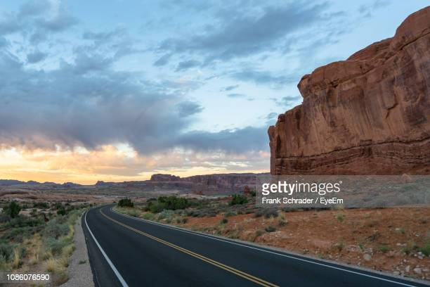 Road At Desert By Mountains Against Sky