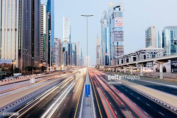 Road at dusk, multiple lane highway, light streaks, skyscrapers,  Dubai