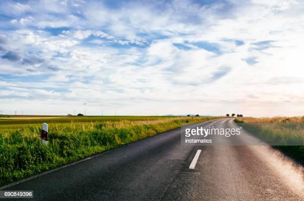 road zwischen den feldern - straßenverkehr stock-fotos und bilder