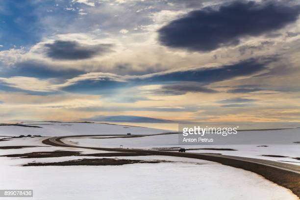 Road between snow-capped hills in northern Norway