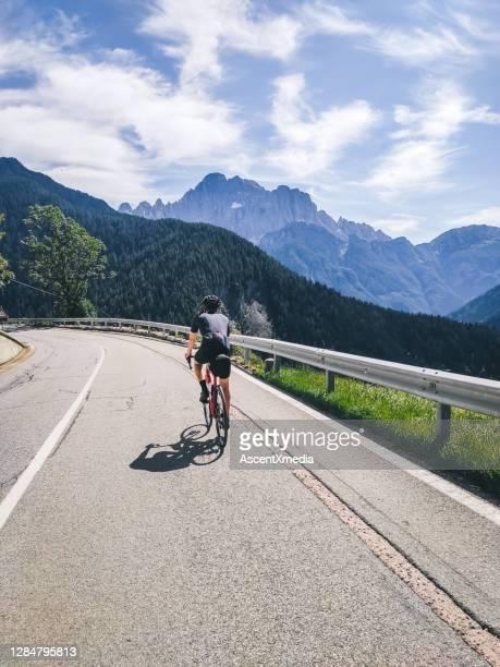 radfahrer fährt an einem schönen tag eine bergstraße hinauf - leitplanke stock-fotos und bilder