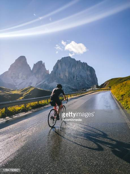 road bicyclist rides up a road in the mountains - forward athlete stock pictures, royalty-free photos & images
