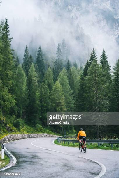 radfahrer fährt im regen auf nasser fahrbahn - leitplanke stock-fotos und bilder