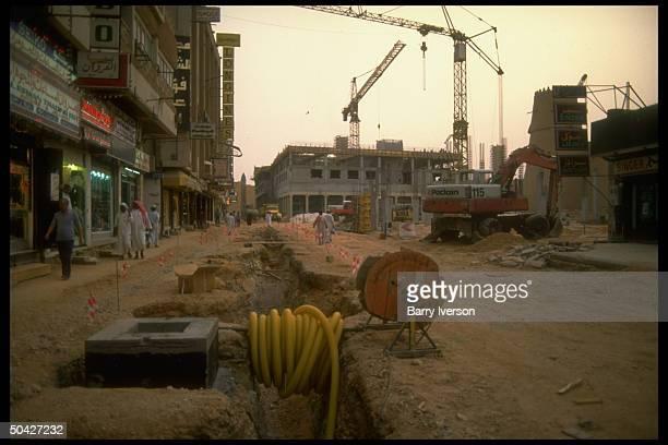 Road bldg construction site w pedestrians traversing narrow strip of storefronted unpaved sidewalk in postgulf war Riyadh Saudi Arabia