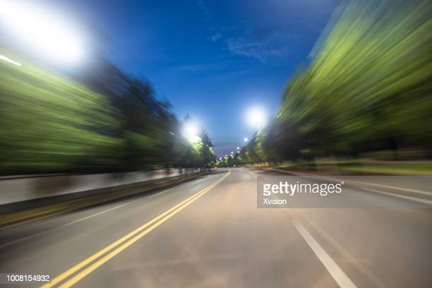 Road blurred at night with street lamp on