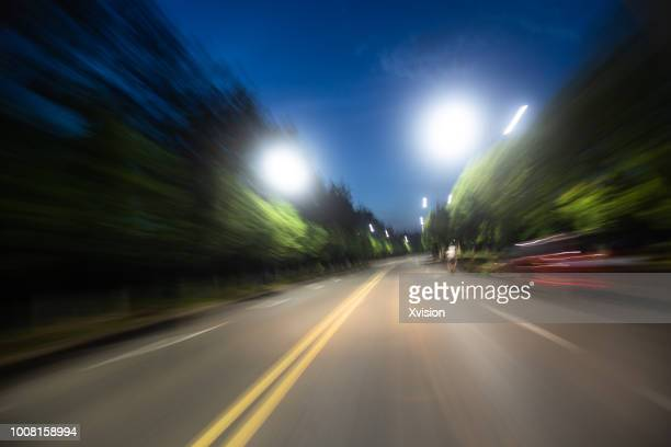 road blurred at night with street lamp on - zoom background stock pictures, royalty-free photos & images