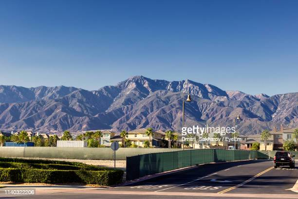 road by buildings against clear blue sky - san bernardino california stock pictures, royalty-free photos & images