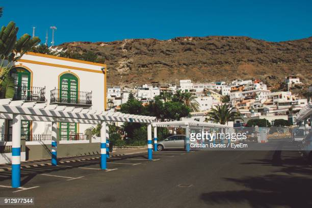 road by buildings against clear blue sky - bortes cristian stock photos and pictures