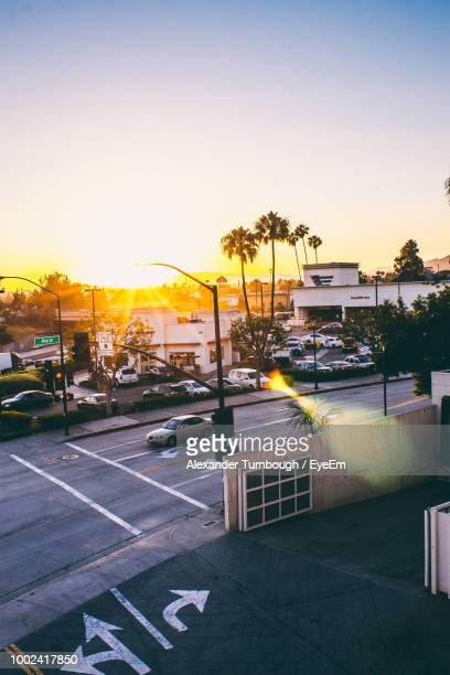road by buildings against sky during sunset in city - san fernando california stock photos and pictures