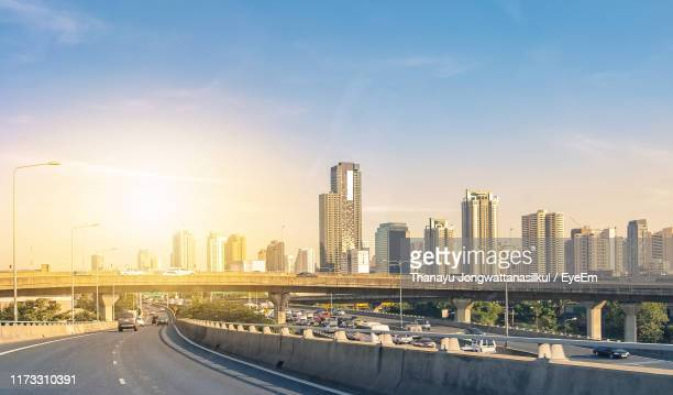 road by buildings in city against sky - billboard highway stock pictures, royalty-free photos & images