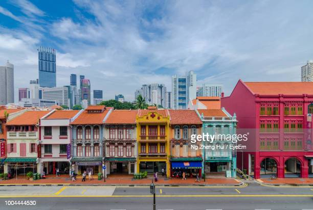 road by colorful buildings against sky in city - chinatown stock pictures, royalty-free photos & images