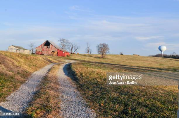 road by house on field against sky - jose ayala stock pictures, royalty-free photos & images