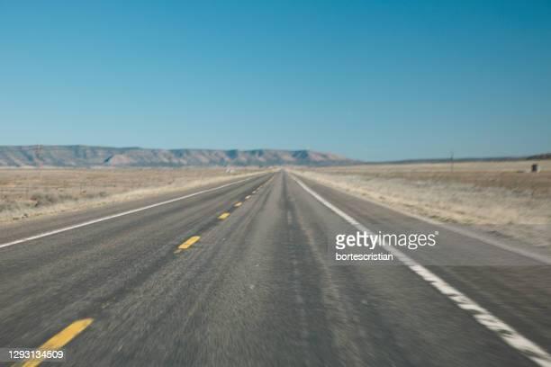road by landscape against clear blue sky - bortes stock-fotos und bilder