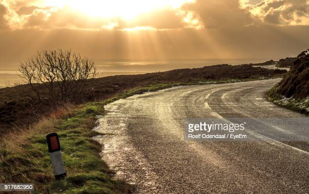 road by landscape against sky during sunset - isle of man stock pictures, royalty-free photos & images