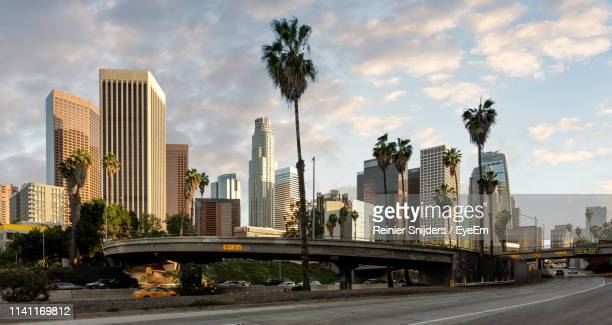 road by modern buildings against sky in city during sunset - de stad los angeles stockfoto's en -beelden