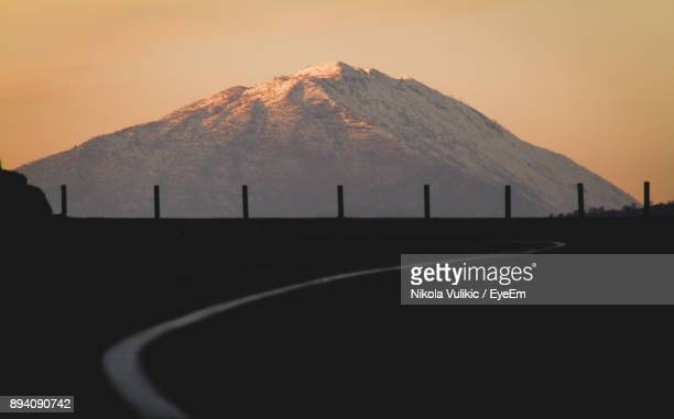Road By Mountain Against Clear Sky During Sunset