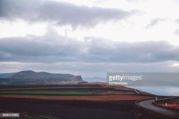 road by mountain against sky - bortes photos et images de collection