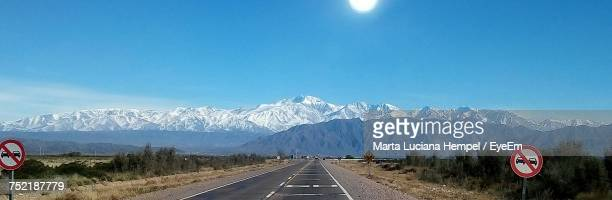 Road By Mountains Against Clear Blue Sky