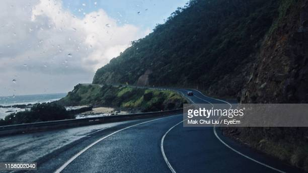 road by mountains against sky seen through vehicle windshield - wet stock pictures, royalty-free photos & images