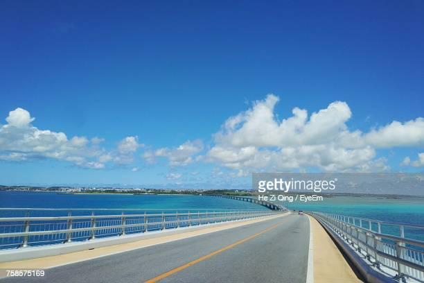 road by sea against blue sky - thoroughfare stock photos and pictures