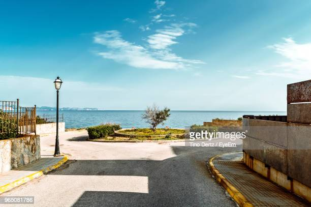 Road By Sea Against Blue Sky