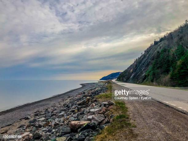 road by sea against sky - cape breton island stock pictures, royalty-free photos & images