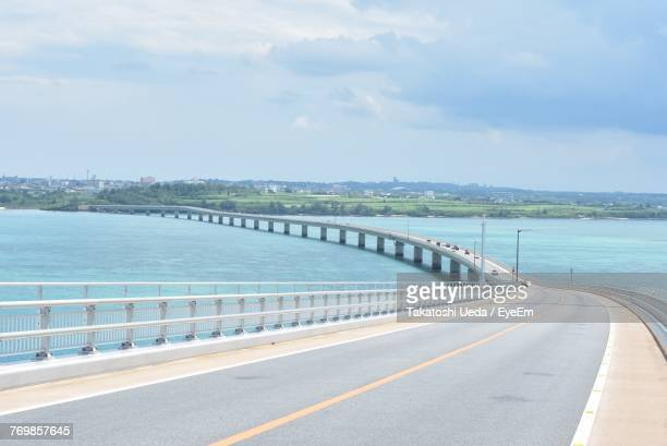 road by sea against sky - 沖縄県 ストックフォトと画像
