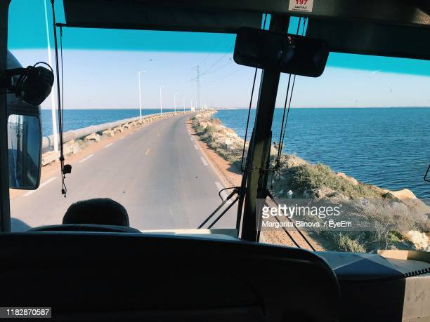 road by sea seen through bus windshield - tunisia stock pictures, royalty-free photos & images