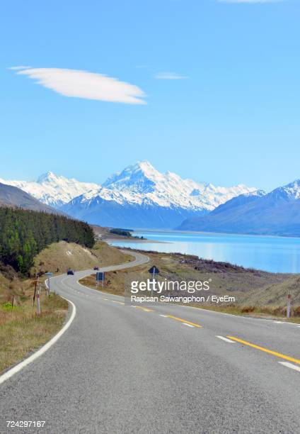 Road By Snowcapped Mountains Against Blue Sky
