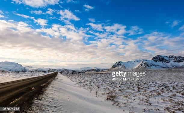 Road By Snowcapped Mountains Against Sky During Winter