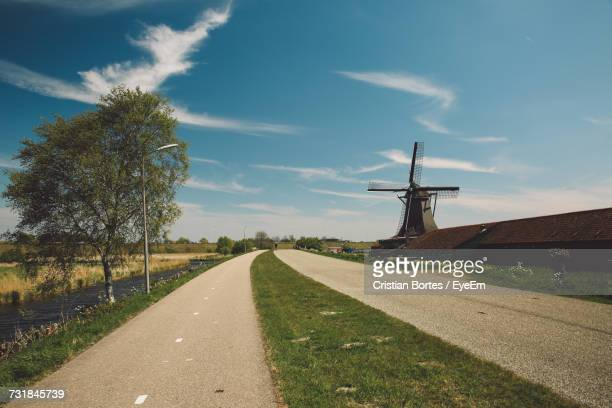 Road By Traditional Windmill Against Sky