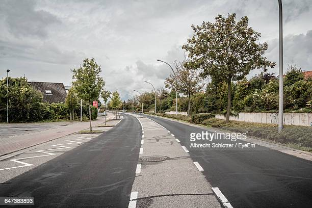 road by trees against cloudy sky - albrecht schlotter stock photos and pictures