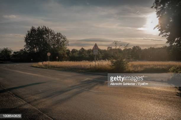 road by trees against sky during sunset - albrecht schlotter stock photos and pictures