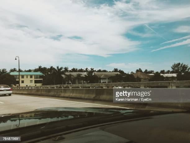 road by trees against sky - delray beach stock photos and pictures