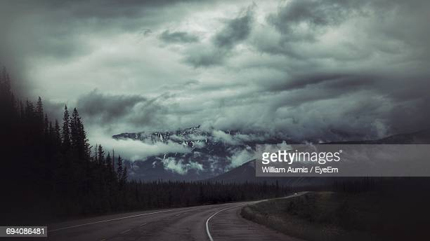 Road By Trees Against Storm Clouds