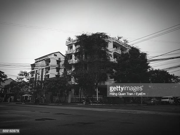 road by trees and building against clear sky - hong quan stock pictures, royalty-free photos & images