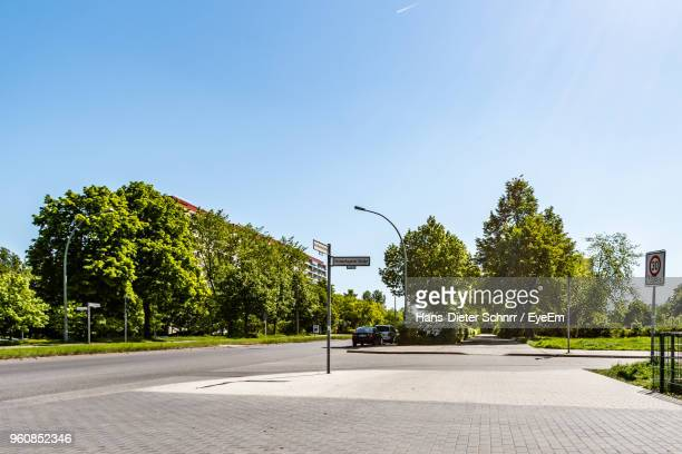 road by trees in city against clear sky - street stockfoto's en -beelden