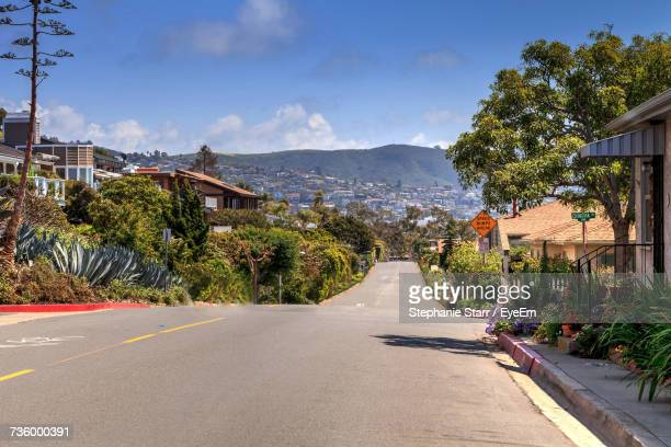 road by trees in city against sky - laguna beach california stock pictures, royalty-free photos & images
