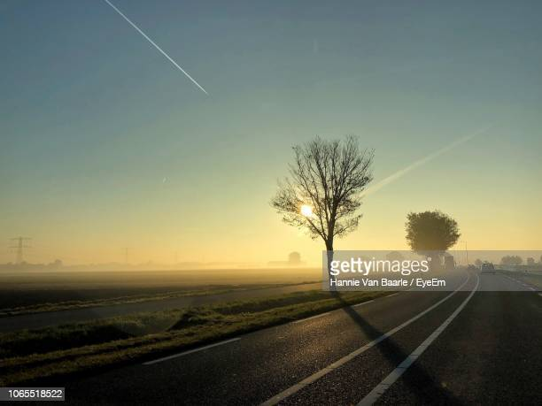 Road By Trees On Field Against Sky At Sunset