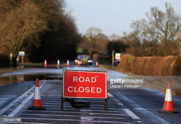 """Road Closed"""" sign stands in front of floodwater after the River Trent burst its banks, near Lowdham, Nottinghamshire, in central England on February..."""