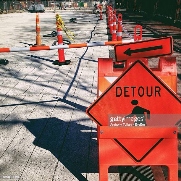 Road closed with detour sign in foreground