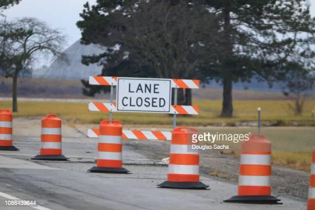 road construction barrier of orange barrels and sign - バリケード ストックフォトと画像