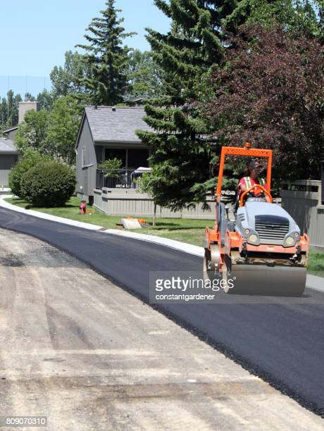 road construction equipment and operator on residential paving project - asphalt paving stock photos and pictures